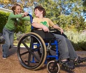 сестра катает брата в инвалидном кресле